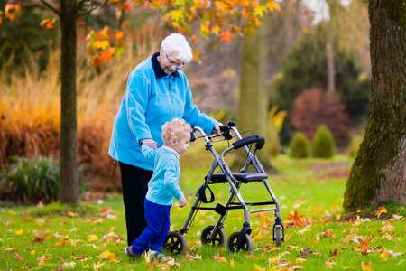 Gelukkige hogere dame met een rollator of een rolstoel en kinderen. Oma en de kinderen genieten van een wandeling in het park. Kind ondersteunen uitgeschakeld grootouder. Familie bezoek. Generaties liefde en relatie.