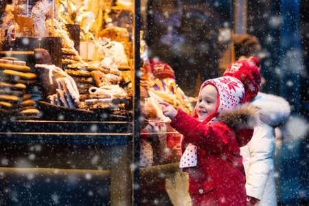 子ウィンドウがドイツの伝統的なクリスマス マーケットでショッピングに雪の降る冬の日。子供たちはお菓子や、パンや菓子のジンジャーブレッド