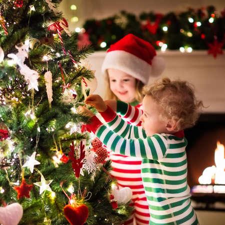 Happy kleine kinderen in de aanpassing van rood en groen gestreepte pyjama's versieren van de kerstboom in de mooie woonkamer met traditionele open haard. Kinderen opening presenteert op kerst vooravond.