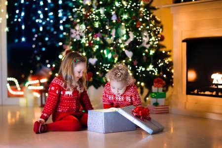 Familia en la víspera de Navidad en la chimenea. Niños abriendo regalos de Navidad. Niños bajo el árbol de Navidad con cajas de regalo. Sala de estar decorada con chimenea tradicional. Acogedor cálido invierno por la noche en casa. Foto de archivo