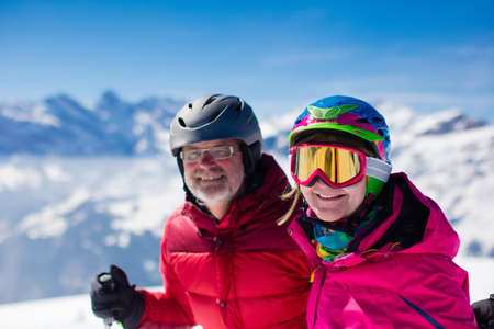 mature women: Happy mature couple skiing in the Alps mountains. Senior man and woman enjoying ski vacation in alpine resort. Active retirement. Healthy winter sport for every age.