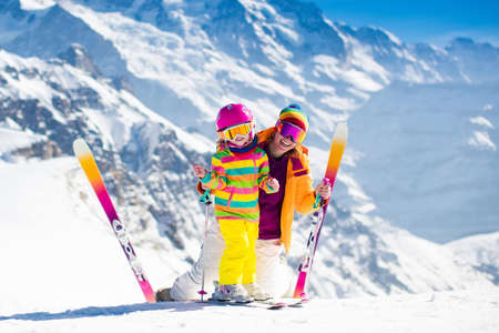 Family ski vacation. Group of skiers in Swiss Alps mountains. Mother and child skiing in winter. Parents teach kids alpine downhill skiing. Ski gear and wear, safe helmets. Banco de Imagens
