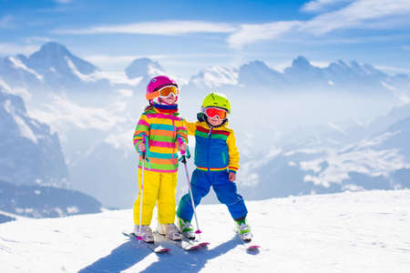 to ski: Kids skiing in mountains. Active children with safety helmet, goggles and poles. Ski race for young kids. Winter sport for family. Child ski lesson in alpine school. Little skier racing in snow