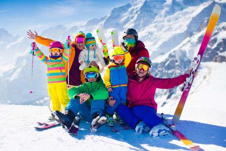 Familie ski-vakantie. Groep van skiërs in Zwitserse Alpen bergen. Volwassenen en jonge kinderen, tiener en baby skiën in de winter. Ouders leren kinderen alpine skiën. Skikleding en slijtage, veilige helmen.