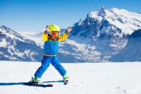 Sci Bambino in montagna. Bambino attivo bambino con casco, occhiali e pali. Gara di sci per i bambini. Sport invernali per la famiglia. Bambini sci lezione a scuola alpina. Piccola corsa sciatore in neve Archivio Fotografico - 63589462