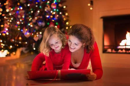 anochecer: Madre e hija leer un libro en la chimenea en la víspera de Navidad. En familia con niño celebración de Navidad. Sala de estar decorada con el árbol, chimenea y velas. Noche de invierno en el hogar para los padres y niños.