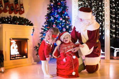 place for children: Children and Santa Claus at fireplace on Christmas eve. Family celebrating Xmas. Decorated living room with tree, gifts, fire place, candles. Winter evening at home for parents and kids.