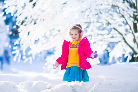 Funny little toddler girl in a colorful knitted hat and warm coat playing with snow. Kids play outdoors in winter. Children having fun at Christmas time. Child enjoying sunny day during Xmas vacation. Stock Photo