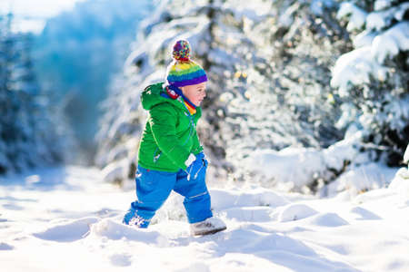 winter park: Child running in snowy forest. Toddler kid playing outdoors. Kids play in snow. Christmas vacation in sunny winter park for family with young children. Little boy in colorful jacket and knitted hat.