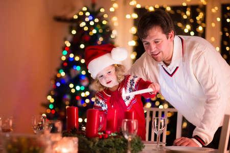 corona de adviento: La cena de Navidad en casa. Niño encendiendo una vela en la corona de adviento en la víspera de Navidad. Sala de estar decorada con chimenea y el árbol. Noche de invierno en la chimenea para una familia con niños. Niños celebrando.