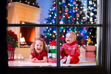 under fire: Familia en la víspera de Navidad en la chimenea. Niños de apertura de Navidad regalos. Los niños menores de árbol de Navidad con cajas de regalo. Sala de estar decorada con chimenea tradicional. Acogedor cálida noche de invierno en casa.