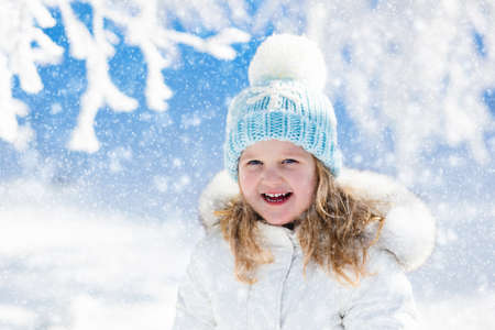 Child in white jacket with fur hood and blue knitted snowflake hat playing in snowy forest on sunny winter day. Toddler kid girl having fun outdoors during Christmas vacation. Kids play in snow. Stock fotó