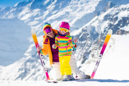 downhill skiing: Family ski vacation. Group of skiers in Swiss Alps mountains. Mother and child skiing in winter. Parents teach kids alpine downhill skiing. Ski gear and wear, safe helmets. Stock Photo