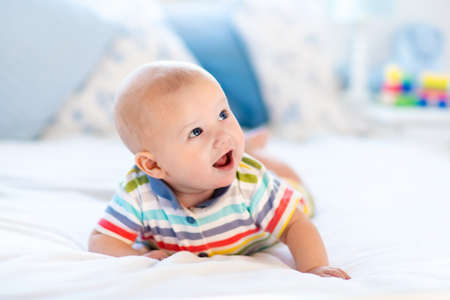 tummy time: Adorable baby boy in white sunny bedroom. Newborn child relaxing in bed. Nursery for young children. Textile and bedding for kids. Family morning at home. New born kid during tummy time with toy bear. Stock Photo