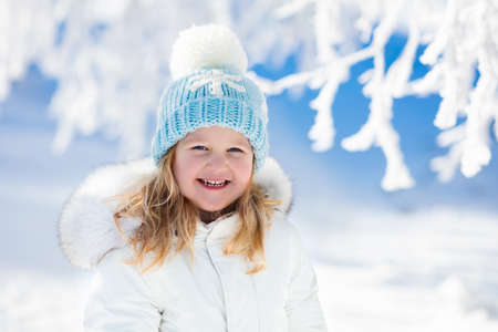 warm clothing: Child in white jacket with fur hood and blue knitted snowflake hat playing in snowy forest on sunny winter day. Toddler kid girl having fun outdoors during Christmas vacation. Kids play in snow. Stock Photo