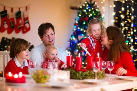Gran familia con tres niños celebrando la Navidad en casa. Cena festiva en la chimenea y el árbol de Navidad. Padres y niños que comen en lugar de fuego en la habitación decorada. Iluminación Niño velas corona de adviento. Foto de archivo - 64548760
