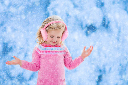 outdoor outside: Little girl in pink knitted sweater and fur earwarmer catching snowflakes in winter park. Kids play outdoor in snowy forest. Children catch snow flakes. Toddler kid playing outside in snow storm.