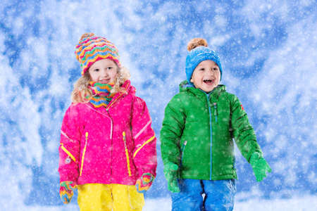 Little girl and boy in colorful hat catching snowflakes in winter park on Christmas eve. Ski vacation for family with children. Kids play outdoor in snowy forest. Children catch snow flake on Xmas. Stock Photo