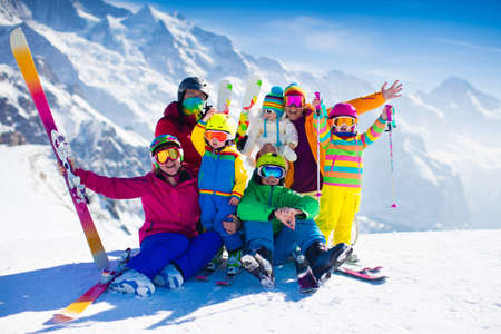gear: Family ski vacation. Group of skiers in Swiss Alps mountains. Adults and young children, teenager and baby skiing in winter. Parents teach kids alpine downhill skiing. Ski gear and wear, safe helmets.