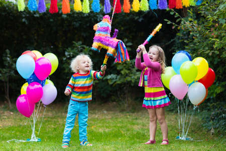 children celebration: Kids birthday party. Group of children hitting pinata and playing with balloons. Family and friends celebrating birthday outdoors in decorated garden. Outdoor celebration with active games.