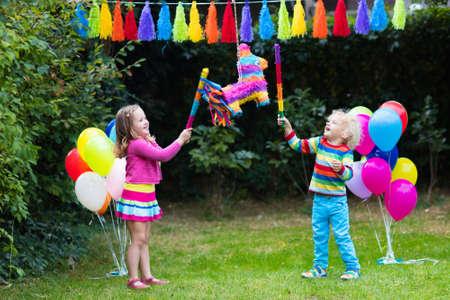 Kinder-Geburtstagsparty. Gruppe von Kindern schlagen Pinata und spielen mit Luftballons. Familie und Freunde Geburtstag im Freien in dekorierten Garten feiern. Outdoor-Feier mit aktiven Spielen. Standard-Bild