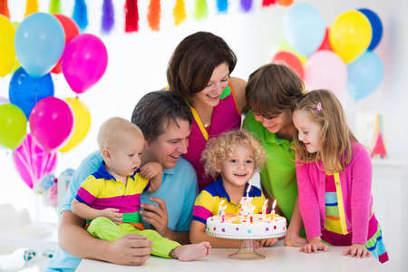 party friends: Family celebrating kids birthday. Parents and children celebrate together. Child party with balloon decoration, cake, candles and presents. Celebration for baby, little boy, girl and school kid