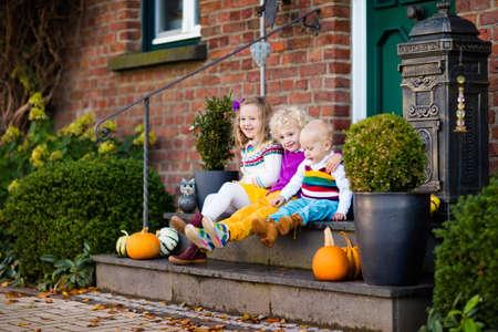 ハロウィーンやサンクスギビングの時に暖かい秋の日に家のドアに石造りの階段に座っているほとんどの子供たちのグループです。秋の庭で遊ぶ子 写真素材