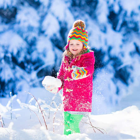 niño corriendo: Child running in snowy forest. Toddler kid playing outdoors. Kids play in snow. Christmas vacation in sunny winter park for family with young children. Little girl in colorful jacket and knitted hat.