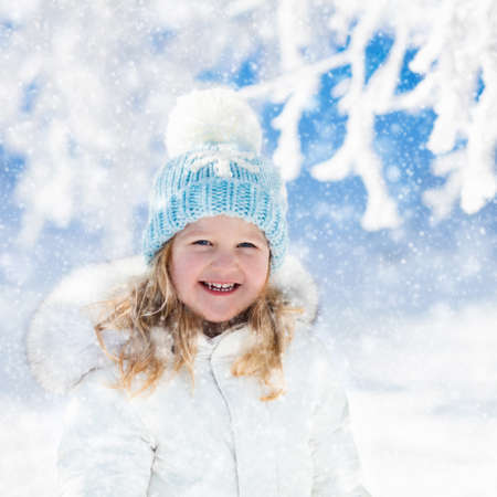 Child in white jacket with fur hood and blue knitted snowflake hat playing in snowy forest on sunny winter day. Toddler kid girl having fun outdoors during Christmas vacation. Kids play in snow. Stock Photo