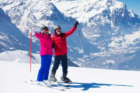幸せな大人のカップルは、アルプス山岳地帯でスキーします。シニアの男と女の高山リゾートでのスキー休暇を楽しんでします。アクティブな退職