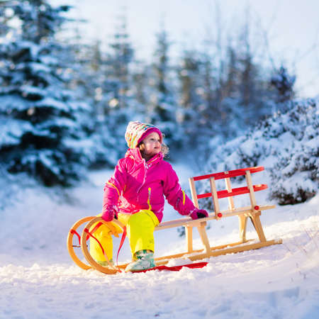 snow  snowy: Little girl enjoying sleigh ride. Child sledding. Toddler kid riding a sledge. Children play outdoors. Kids sled in snowy park in winter. Outdoor fun for family Christmas vacation. Fir trees and snow. Stock Photo