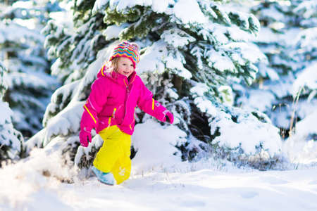 winter vacation: Child running in snowy forest. Toddler kid playing outdoors. Kids play in snow. Christmas vacation in sunny winter park for family with young children. Little girl in colorful jacket and knitted hat.