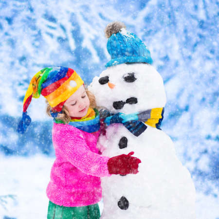 having fun in winter time: Funny little toddler girl in a colorful hat and warm coat playing with a snow man. Kids play outdoors in winter. Children having fun at Christmas time. Child building snowman at Xmas.
