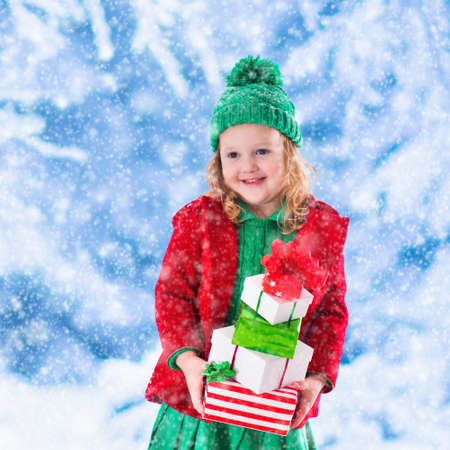Little girl in red and green knitted hat holding Christmas present boxes in winter park on Xmas eve. Kids play outdoor in snowy winter forest. Children opening presents. Toddler kid playing with gifts Stock Photo