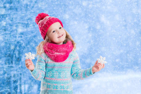 outdoor outside: Little girl in blue knitted sweater and pink hat catching snowflakes in winter park. Kids play outdoor in snowy forest. Children catch snow flakes. Toddler kid playing outside in snow storm.