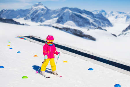 kids at the ski lift: Child in alpine ski school with magic carpet lift and colorful training cones going downhill in the mountains on a sunny winter day. Little skier kid learning and exercising skiing on a slope. Stock Photo