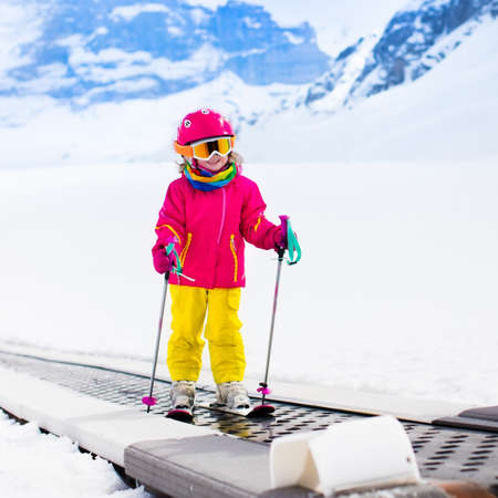 kids at the ski lift: Child on magic carpet ski lift going uphill in the mountains on snowy winter day. Kids in winter sport school in alpine resort. Family fun in the snow. Little skier learning and exercising on a slope. Stock Photo