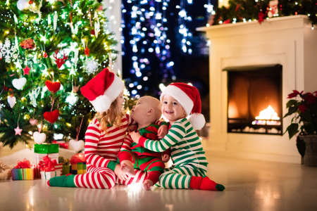 place of living: Happy little kids in matching red and green striped pajamas decorate Christmas tree in beautiful living room with traditional fire place. Children opening presents on Xmas eve.