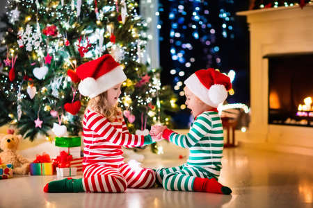 striped pajamas: Happy little kids in matching red and green striped pajamas decorate Christmas tree in beautiful living room with traditional fire place. Children opening presents on Xmas eve.