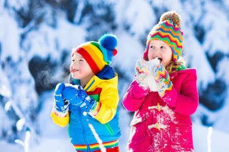 Kinderen spelen in besneeuwd bos. Peuter kinderen buiten in de winter. Vrienden die in sneeuw spelen. Kerstvakantie voor gezin met jonge kinderen. Klein meisje en jongen in kleurrijke jas en gebreide muts.