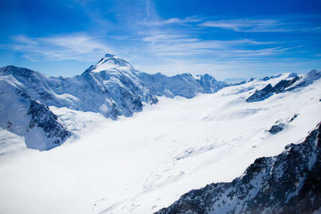 Aerial view of the Alps mountains in Switzerland. View from helicopter above glacier in Swiss Alps. Mountain tops covered in snow. Alpine ski facilities from above.