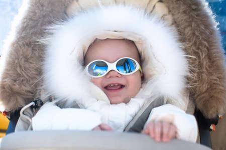 gafas de sol: El pequeño bebé en cochecito caliente que desgasta el juego de la nieve capucha de piel que disfruta de vacaciones de esquí en invierno estación alpina. Gafas y gafas de sol de protección solar para los niños. Niño en gafas de nieve seguras en montañas de los Alpes.