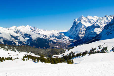 Alpine ski facility in Swiss Alps. Landscape of Switzerland on sunny day. Snow covered Alps mountain peaks. Ski trip in Swiss Alps. Landscape with valley, village and mountains. Stock Photo