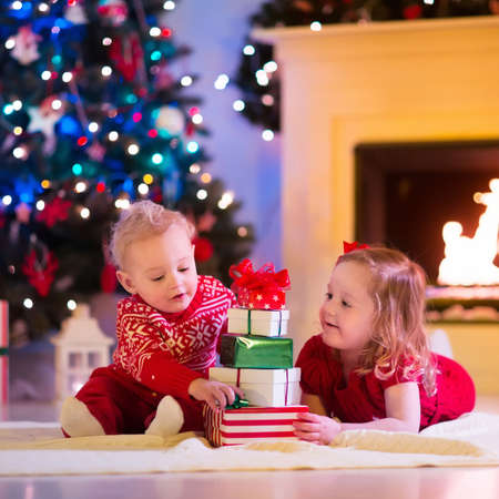 Familia en la víspera de Navidad en la chimenea. Niños de apertura de Navidad regalos. Los niños menores de árbol de Navidad con cajas de regalo. Sala de estar decorada con chimenea tradicional. Acogedor cálida noche de invierno en casa.