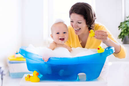 Happy baby taking a bath playing with foam bubbles. Mother washing little boy. Young child in a bathtub. Smiling kids in bathroom with toy duck. Mom bathing infant. Parent and kid play with water. Archivio Fotografico