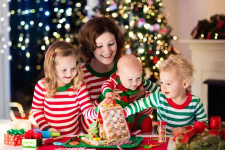 neige noel: famille heureuse, jeune mère avec un bébé, petit garçon et une fille faisant maison en pain d'épice au foyer dans la décoration salon avec arbre de Noël. La cuisson et la cuisine avec les enfants pour Noël à la maison.