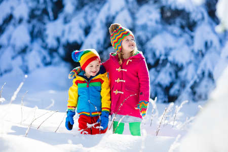 Children play in snowy forest. Toddler kids outdoors in winter. Friends playing in snow. Christmas vacation for family with young children. Little girl and boy in colorful jacket and knitted hat. Stock Photo