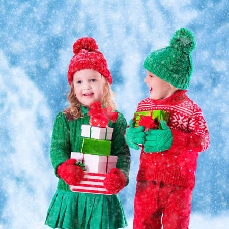 Little girl and boy in red and green knitted hat holding Christmas present boxes in winter park on Xmas eve. Kids play outdoor in snowy winter forest. Children opening presents. Panorama size. Stock Photo