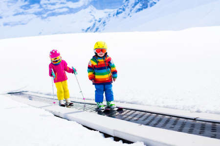 kids at the ski lift: Children on magic carpet ski lift going uphill in the mountains on snowy winter day. Kids in winter sport school in alpine resort. Family fun in the snow. Little skier exercising on a slope. Stock Photo
