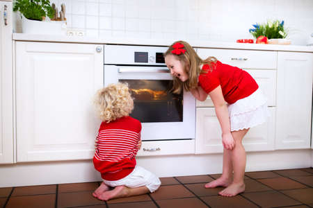 kitchen device: Little boy and girl, brother and sister baking delicious apple pie in white kitchen. Kids looking at fruit cake in the oven. Children bake at home. Toddler child and preschooler waiting for pastry. Stock Photo